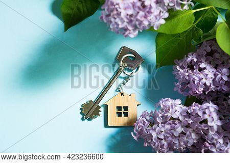 House Key With Keychain On Blue Spring Background And Lilac Branches.summer Holiday Home, Booking Co