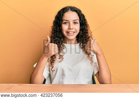 Teenager hispanic girl wearing casual clothes sitting on the table success sign doing positive gesture with hand, thumbs up smiling and happy. cheerful expression and winner gesture.