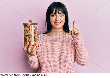 Young hispanic woman holding jar with uncooked pasta smiling with an idea or question pointing finger with happy face, number one