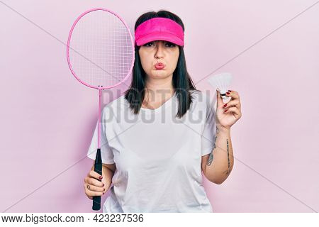 Young hispanic woman holding badminton racket and shuttlecock depressed and worry for distress, crying angry and afraid. sad expression.
