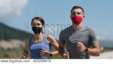Young man and woman in protective masks running and doing exercises outdoors in the morning. Sport, Active life Jogging during quarantine. Covid-19 new normal. Selective focus.