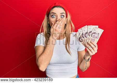 Young caucasian woman holding 500 mexican pesos banknotes covering mouth with hand, shocked and afraid for mistake. surprised expression