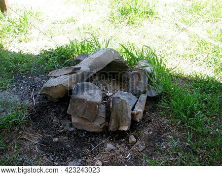 An Extinct Stone Round Hearth Outside Among The Green Grass.