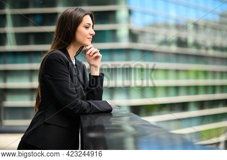 Smiling businesswoman poirtrait in a pensive expression leaning on a balcony, dominating the city from above