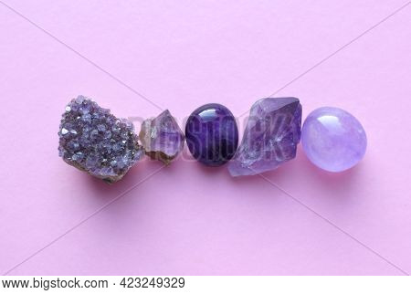 Gemstone Minerals On A Pink Background. Round Tumbling Minerals Of Amethyst And Amethyst Crystal.