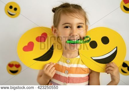 World Smile Day. Anthropomorphic Smile Face. A Little Girl With A Smiling And Loving Cardboard Emoti