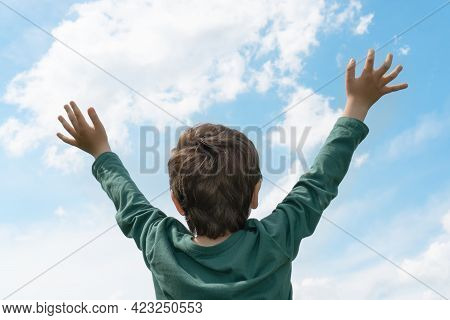 Relaxed Boy Raising His Hands To The Blue Sky In Sunny Day, Embracing Nature. Loving Nature, Freedom