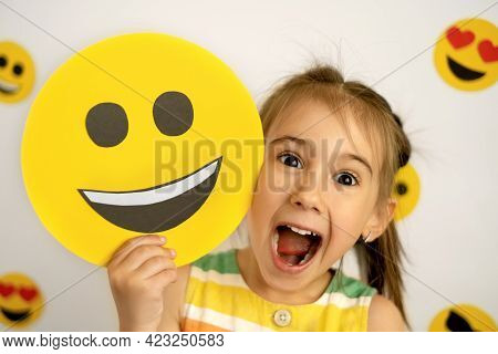 World Smile Day. Anthropomorphic Smile Face. A Little Girl With A Smiling Cardboard Smile Face Is La