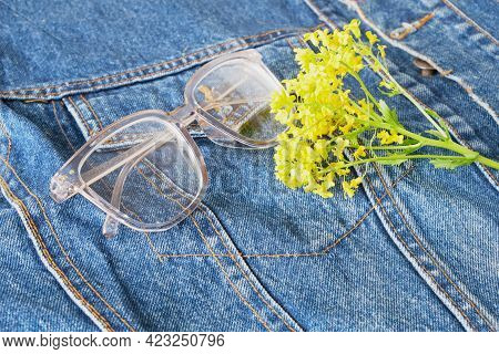 Yellow Wildflowers And Eye Glasses With Transparent Frames On The Pocket Of Blue Denim Jacket, Trend