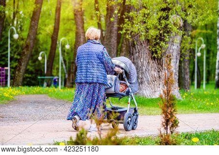 Woman Wheeling A Pram In The Park
