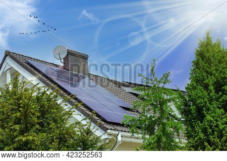 Solar Panels On The Roof. Beautiful Modern House And Solar Energy. Nature Sun Rays And Trees.