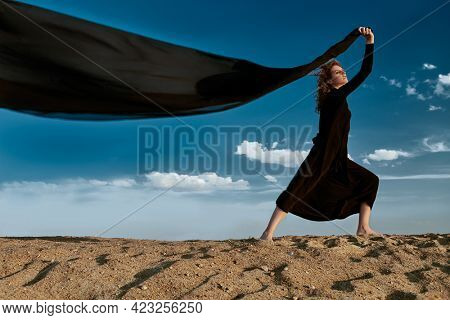 Beautiful brunette woman in a long black dress posing in the desert with a scarf fluttering in the wind. Fashion shot. Sky background.