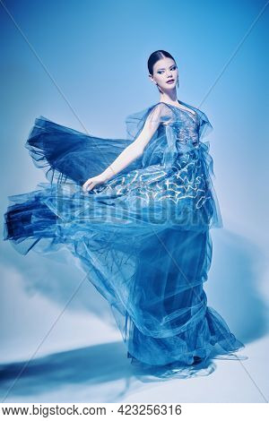Beautiful female ballet dancer  dancing in a luxury evening dress. Fashion and beauty concept. Ballet show. Full length studio portrait.