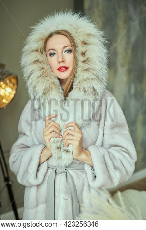 Beautiful blonde woman in an expensive mink and lynx fur coat posing in an apartment with a classic luxury interior. Fur coat fashion.