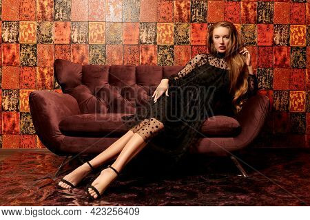 Glamorous lifestyle. Beautiful young woman in black evening dress sits on a sofa in luxury apartments. Beauty, fashion. Modern interior, furniture.