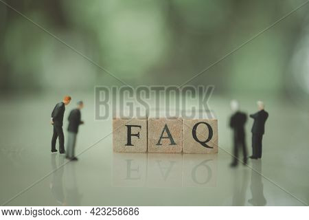 Miniature Businessman And Faq Letters Wooden Block Word. Faq Direction And Business Man