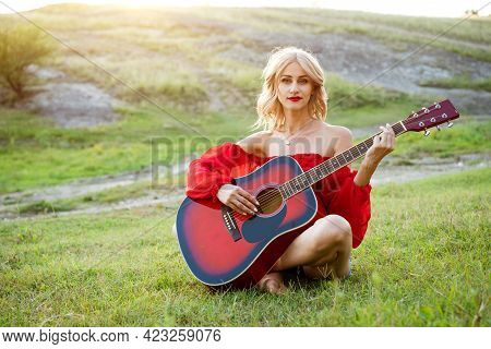 Woman In Red Grass With A Red Guitar. Girl Musician Plays The Guitar Outdoors. Blonde Caucasian Appe