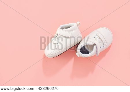 Baby First Shoes On Pink Pastel Background. Family Or Motherhood Concept.