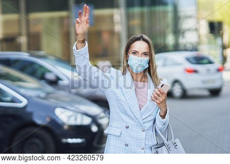 Business woman in mask catching a taxi in the city