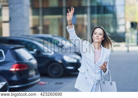 Business woman catching a taxi in the city