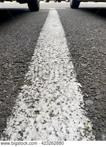 White Parking Lane Line With Two Wheels On Background