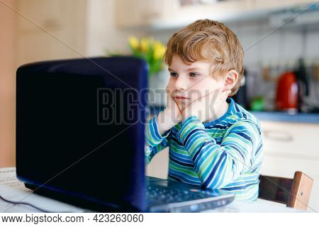 Kid Boy Learning At Home On Laptop For School. Elementary School Child Making Homework And Using Not