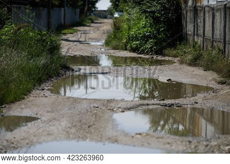 Shallow Depth Of Field (selective Focus) Details With Huge Potholes Filled With Water After A Rain I