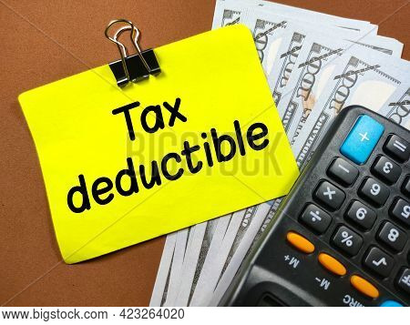 Business Concept.text Tax Deductible On Sticky Note With Calculator And Banknote On Brown Background