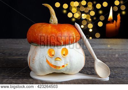A Creepy Smiling Halloween Pumpkin With A Burning Candle Flame. Orange Nightmare On A Wooden Table