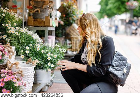 Young Business Woman Choosing Flowers In Flower Shop. Happy Alone Woman In In The City On Sunny Summ
