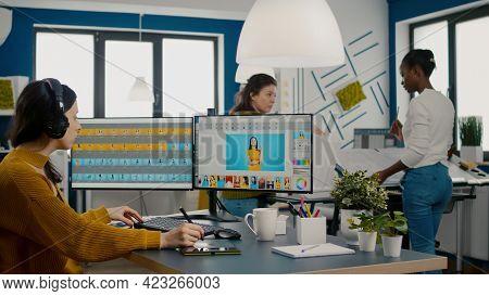 Retoucher Putting On Headphones Retouching Image Using Stylus Pen, Listening Music While Working On