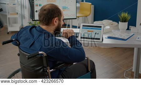 Disabled Handicapped Immobilized Paralyzed Manager Man Using Computer And Tablet In Same Time Workin