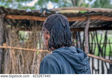 Profile of African man with dreadlocks , portrait standing in his yard in a village in Botswana