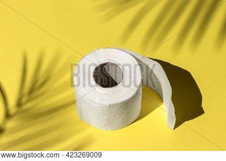 Roll Of A White Toilet Paper Isolated On A Yellow Background Under A Palm Tree Shadow Close-up. Hard
