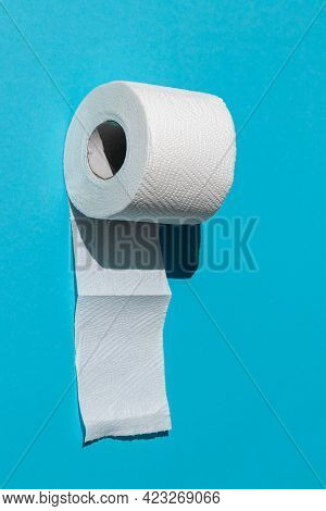 Roll Of A White Toilet Paper Isolated On A Blue Background Close-up. Hard Shadows From The Sun At No