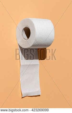 Roll Of A Perforated Toilet Paper Isolated On A Sand Color Background Close-up. Hard Shadows From Th