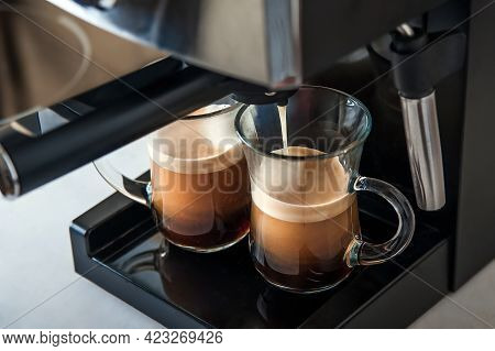 Two Transparent Cups Coffee Close-up Front View. Home Coffee Maker And Process Of Making Coffee Drin