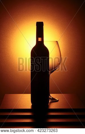 Bottle Of Red Wine And An Empty Glass. Yellow Backlight.
