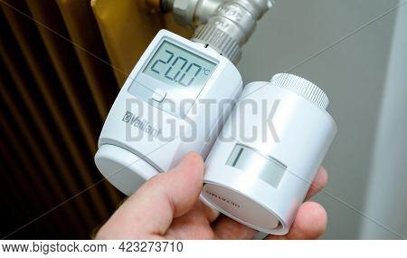 Paris, France - Apr 21, 2021: Pov Male Hand Holding Netatmo By Stark Intelligent Radiator Thermostat