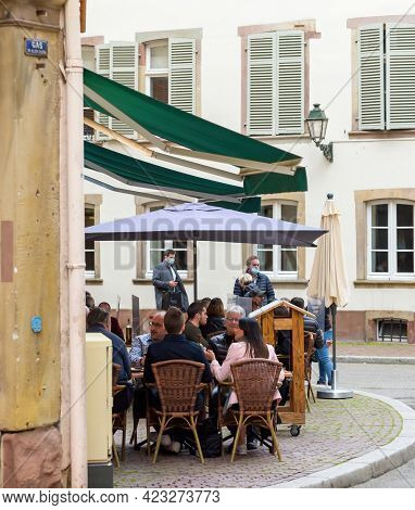 Strasbourg, France - May 19, 2021: Side View Of Young People Eating Drinking At The Terrace Of Frenc