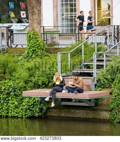 Strasbourg, France - May 20, 2021: Couple Eating Take Away Asian Food Over The Ill River