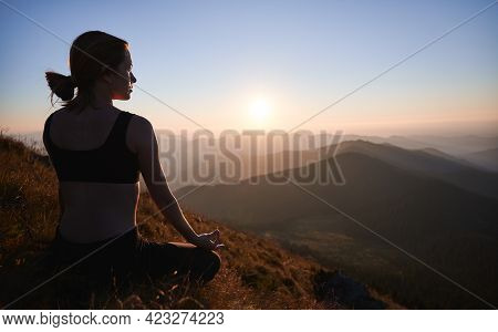 Back View Of Fit Young Woman Sitting In Lotus Position And Meditating While Looking At Beautiful Sun