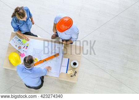 Top View Of Engineers Team Meeting For Architectural Project. Architects Discussing Blueprint With C