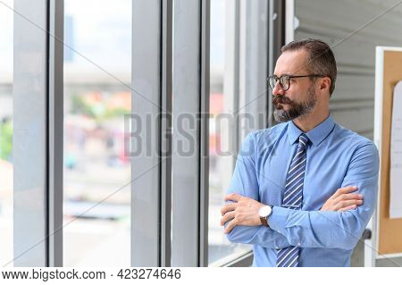 Portrait Of Confident Middle-aged Businessman In Blue Shirt And Wearing Glasses With A Beard And Mus