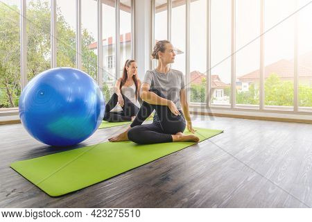 Two Young Beautiful Women Practicing Yoga Lesson On Yoga Mat, Meditating In Living Room At Home. Hea