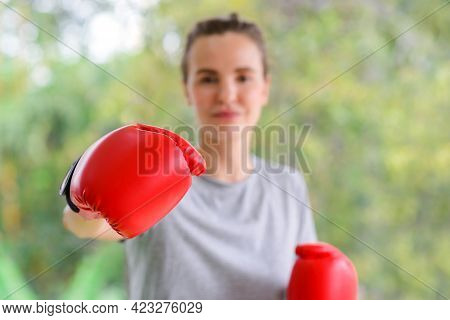 Portrait Of Young Fitness Sporty Woman In Sportswear With Red Boxing Gloves Punching Hit. Select Foc