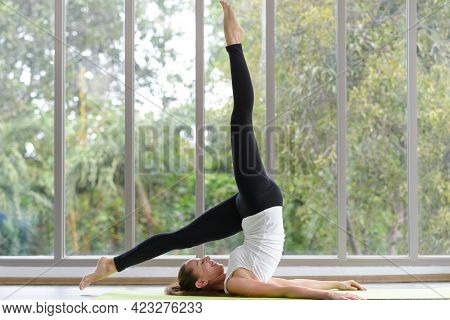 Young Beautiful Woman Practicing Yoga Lesson On Yoga Mat, Meditating In Living Room At Home. Healthy