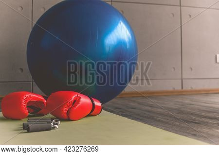 Boxing Gloves, Heavy Grip And Fitness Ball In Sport Gym With Copy Space. Composition Of Different Sp