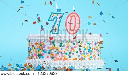 Colorful tasty birthday cake with candles shaped like the number 70.
