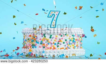 Colorful tasty birthday cake with candles shaped like the number 7.